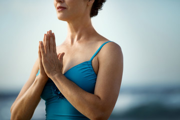 Serene mid-adult woman practicing yoga on a beach.
