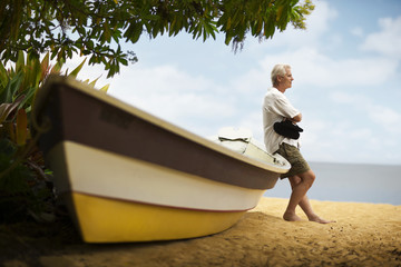 Man leans against his boat on the beach.