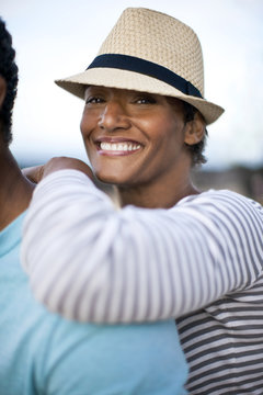 Portrait of mature woman smiling, leaning on her husband's back.