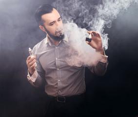 vaper man holding e-liquid, .Stop smoking start vaping tasty e-liquid or e-juice liquid.Vaping device is very popular gadget