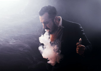 Man coughing out vaponizer holding a vape mod in his hand.