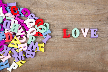 "Text ""Love"" of colored wooden letters on a wooden background"