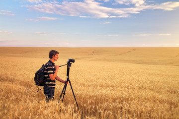 Photographer takes pictures in a wheat field.