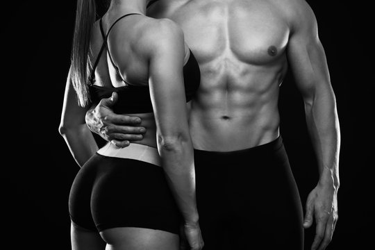 Young sporty couple posing on black background. Black and white photo