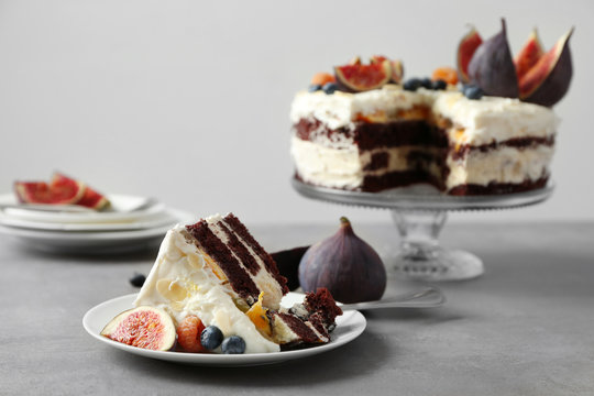 Delicious creamy cake with figs and berries on light grey background