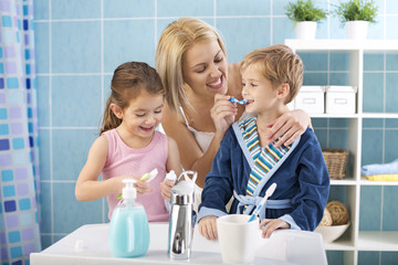 Mother and children brushing teeth.
