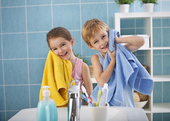 Children washing faces in the bathroom.