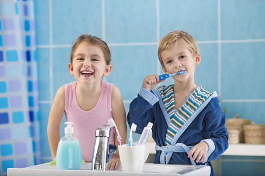 Children brushing teeth in the bathroom.