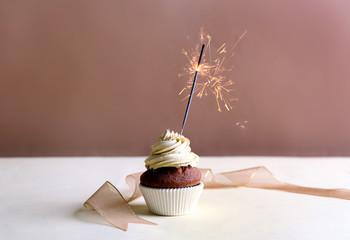 Birthday cupcake with sparkler on beige background