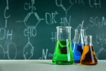 Test beakers and flasks on blackboard background