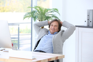 Positive mature man resting in office