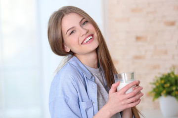 Beautiful young woman with glass of milk at home