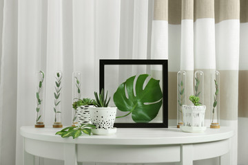 Floral composition with green leaves on table near window
