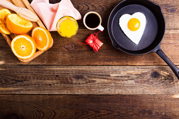Heart shape fried egg, fresh orange juice and coffee. Top view