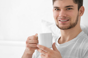 Handsome young man drinking coffee at home