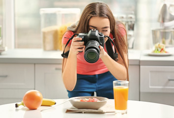 Young pretty woman photographing food in kitchen