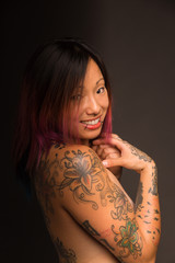 Athletic young asian woman with tattoos and colored hair stands topless and smiles