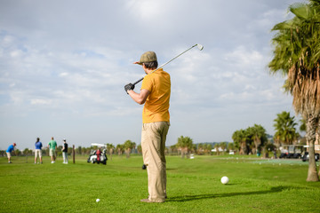 Back view of man on green grass golf field natural outdoors background