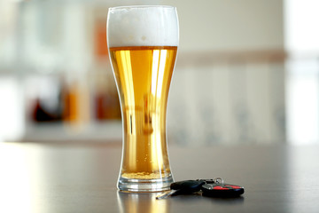 Glass of beer and car key on table. Don't drink and drive concept