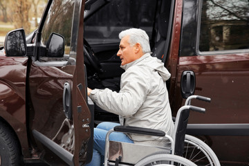 Man in a wheelchair next to his car