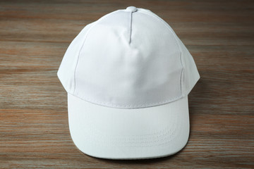 Blank white baseball cap on wooden background