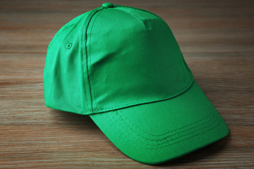 Blank green baseball cap on wooden background