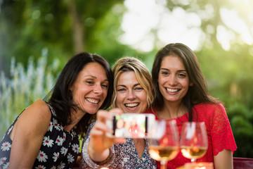 TThree beautiful women having fun by taking a selfie