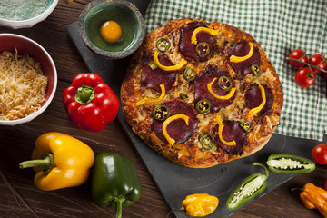 Tasty pizza, tomatoes and others ingredients on a wooden backgro