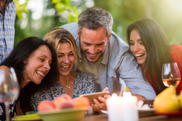 Group of friends having fun by watching photos on a smartphone