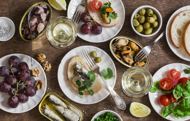 Seafood snacks table - canned sardines, mussels, octopus, grape, olives, tomato and two glasses white wine on wooden table, top view. Flat lay