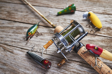 antique fishing lures and reel on a wood table