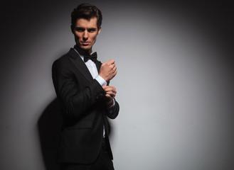 man in tuxedo arranging his sleeve looks back over shoulder