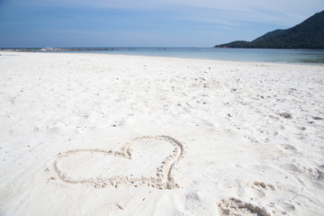 Heart in sand on a perfect deserted white sand beach with the tropical sea (Malibu Beach, Koh Phangan Island, Thailand).