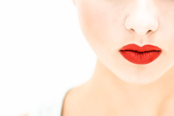 Close-up. Woman with red lips on a light background