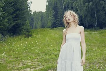 Beautiful woman outdoors enjoying nature in dress at summer meadow