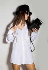 naked girl in a man's white shirt, sunglasses and black hat, holding camera