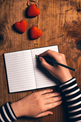 Woman writing love letter card for Valentines day