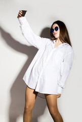 naked girl in a man's white shirt and sunglasses, holding phone, doing selfie.