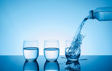 Bottle with creative splashing water in the glass