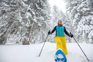 Joyful woman runs on snowshoes through the coniferous forest