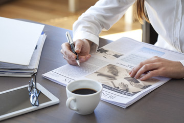 Woman reading newspaper on table
