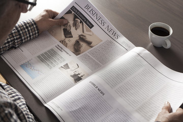 Senior man reading newspaper on table