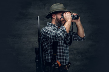 A hunter holds a rifle. Wall mural