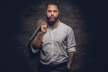 Bearded black man with tattooed arm.
