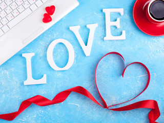 Valentines background with red heart, coffee cup and laptop. Valentines Day greeting card. Female workplace