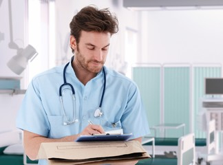Doctor filling out patient record in hospital