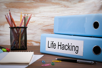 Life Hacking, Office Binder on Wooden Desk. On the table colored pencils, pen, notebook paper.