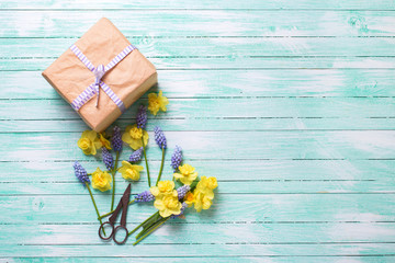 Fresh yellow and blue spring flowers and box with present on tur