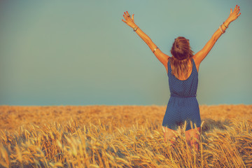 Girl enjoying in a wheat-field.
