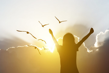 Lady or female young girl hand up with group of bird on sky and clouds wit